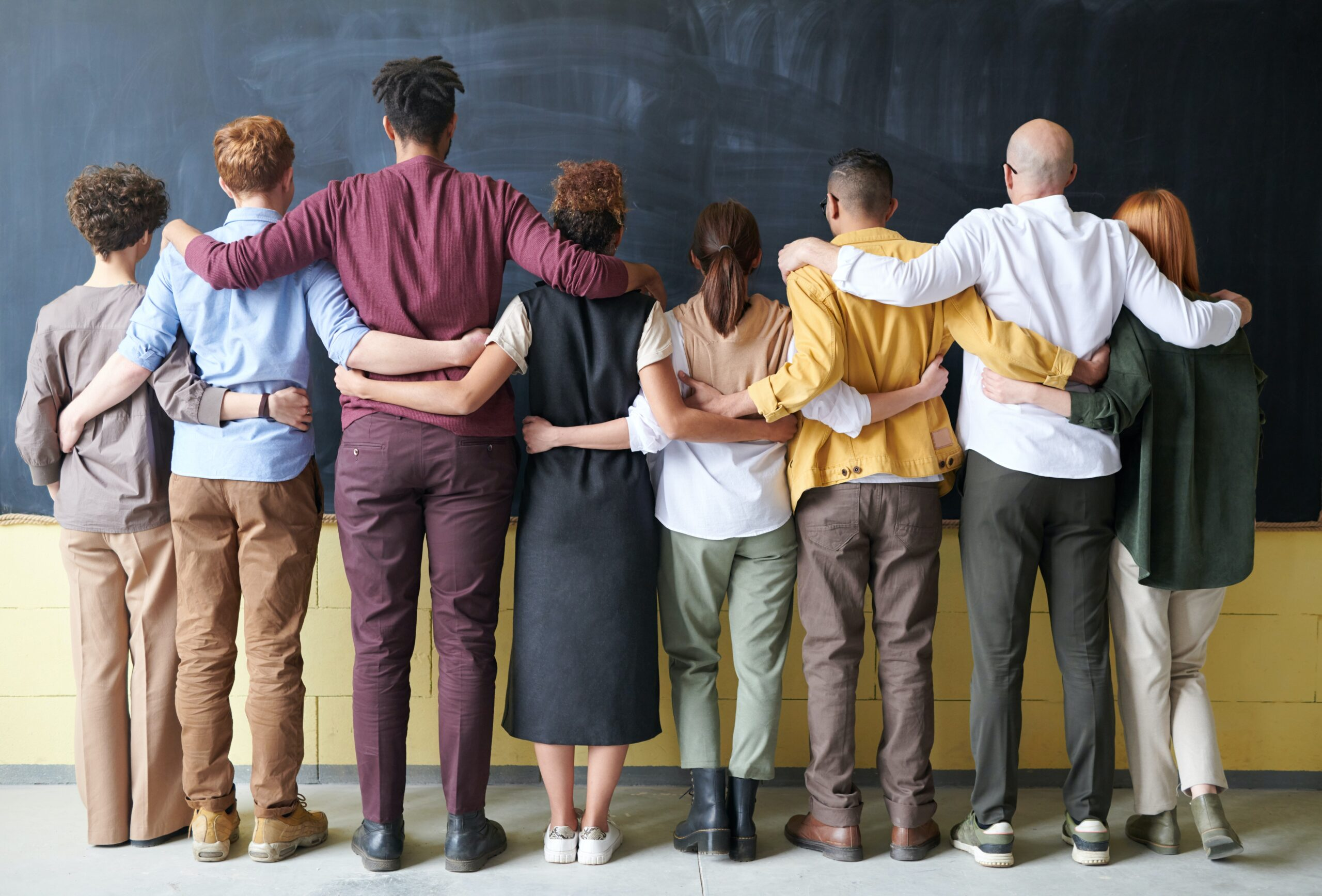 A group of people stand with their backs to the camera and their arms around each other