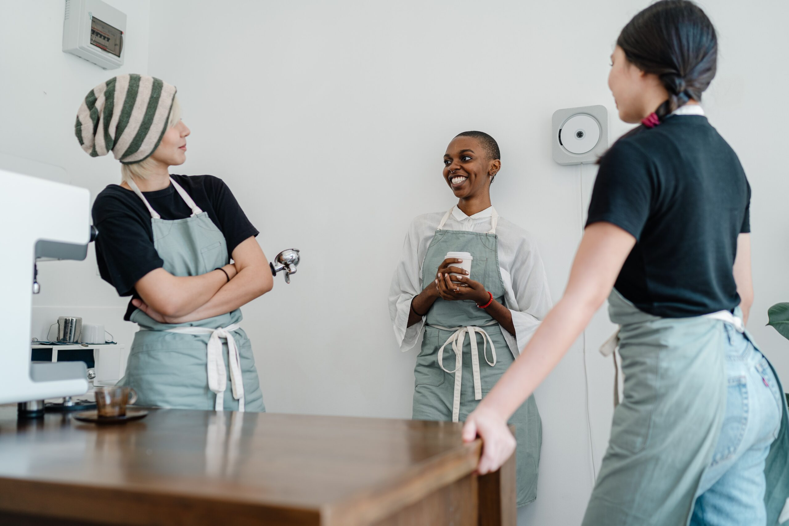 Three people wearing aprons stood in a kitchen talking