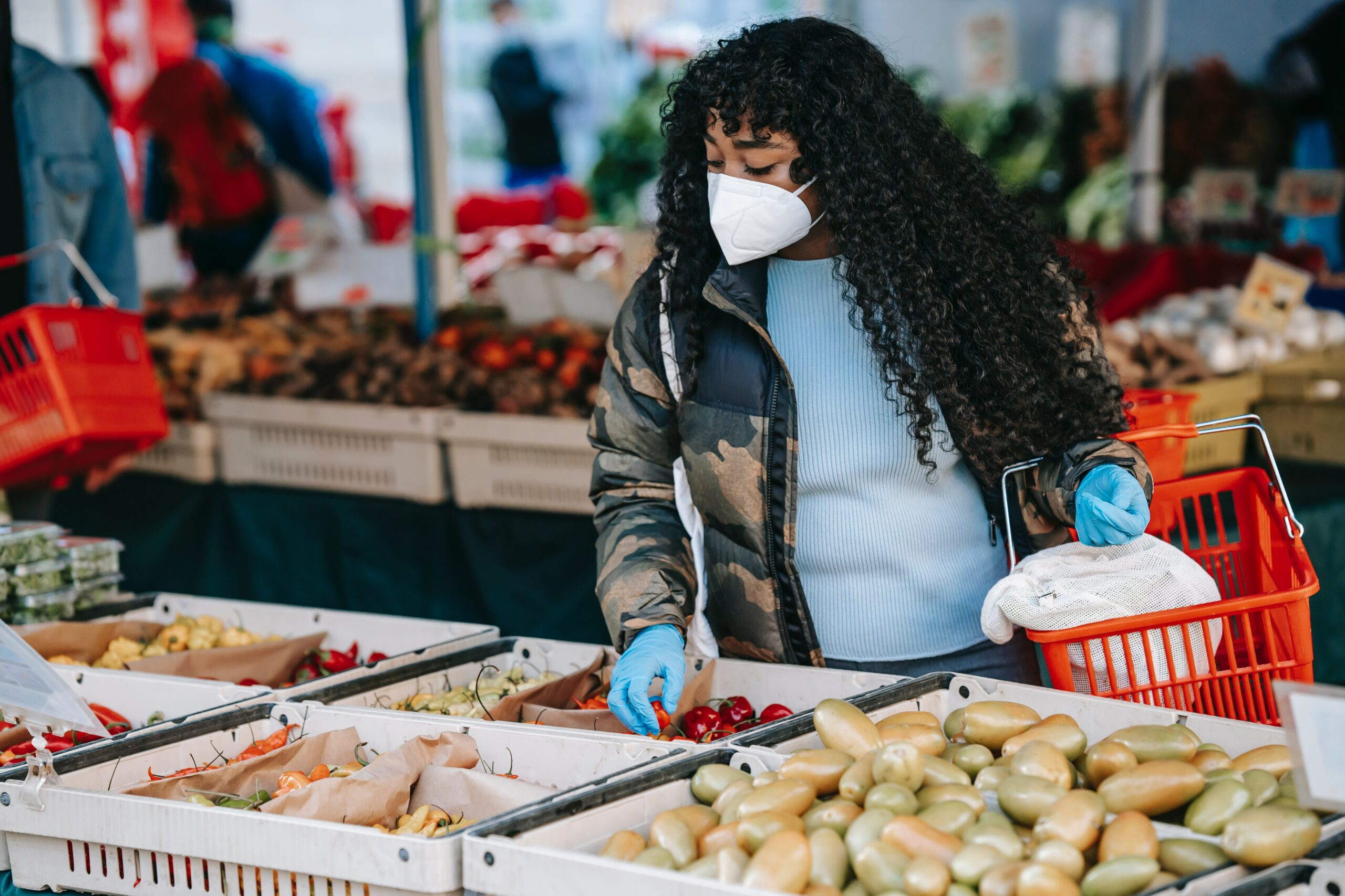 A woman holding a basket and browsing vegetables at a market whilst wearing a mask and latex gloves